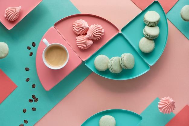 Геометрический бумажный стол в мятно-коралловых тонах с кофе и сладостями.