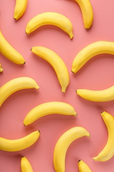 Geometric pattern of bananas on a pink background. the view from the top. minimal flat style. pop art design, creative summer concept.