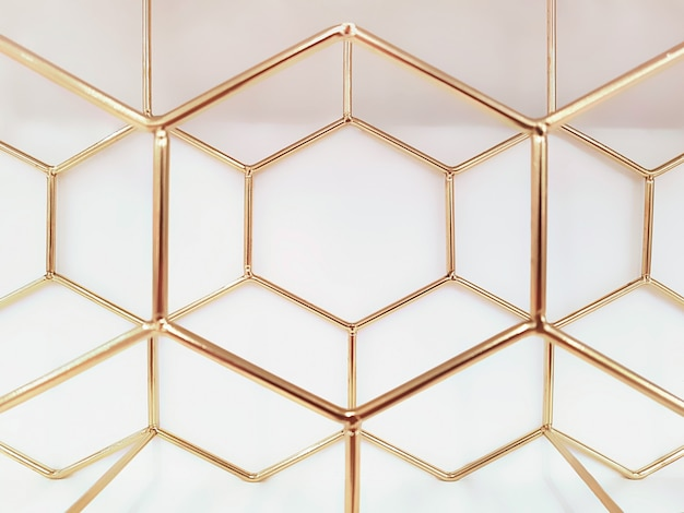 Geometric pattern of hexagons made of metal in gold color . concept , abstraction