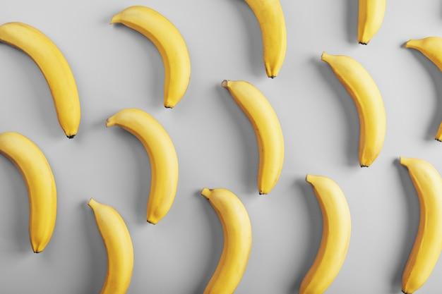 회색 배경에 바나나의 기하학적 패턴입니다. 상단에서보기. 최소한의 평면 스타일.