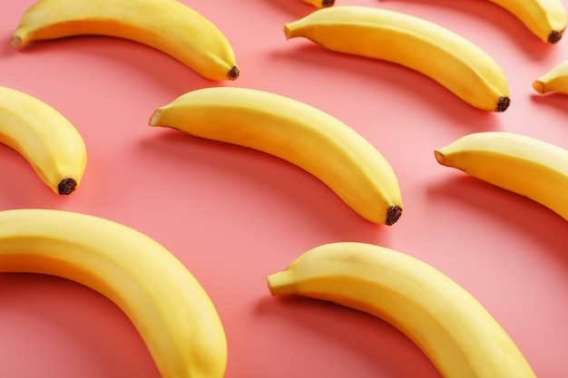 ピンクの背景にバナナの幾何学模様。上からの眺め。最小限のフラットスタイル。ポップアートのデザイン、クリエイティブな夏のコンセプト。
