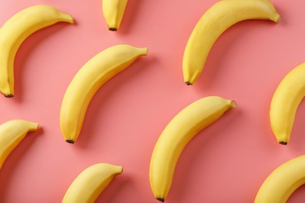 Геометрический узор из бананов на розовом фоне.