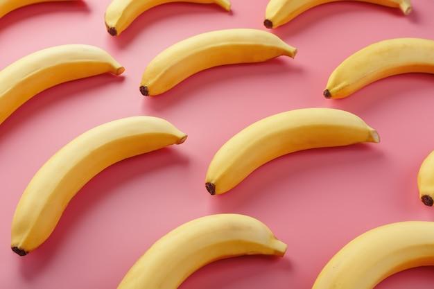 ピンクのテーブルの上のバナナの幾何学模様。上からの眺め。最小限のフラットスタイル。ポップアートのデザイン、創造的な夏のコンセプト。