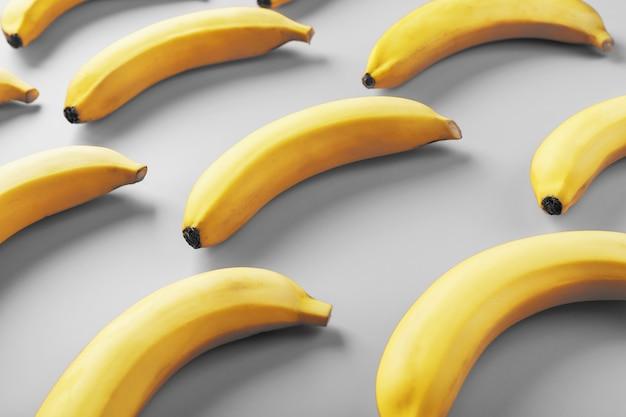 2021年のファッショナブルな色の灰色の背景に黄色のバナナの幾何学模様