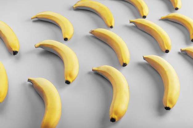2021年のファッショナブルな色の灰色の表面上の黄色いバナナの幾何学模様。上面図