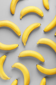Geometric pattern of yellow bananas on a gray background in the fashionable colors of 2021.