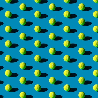 Geometric seamless pattern of tennis balls with strong shadows on a blue