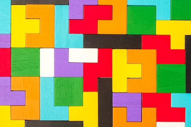 다채로운 나무 퍼즐 조각 배경으로 기하학적 모양 블록. 논리적 사고, 비즈니스 논리, 수수께끼, 결정, 솔루션, 합리적, 사명, 성공, 목표 및 전략 개념