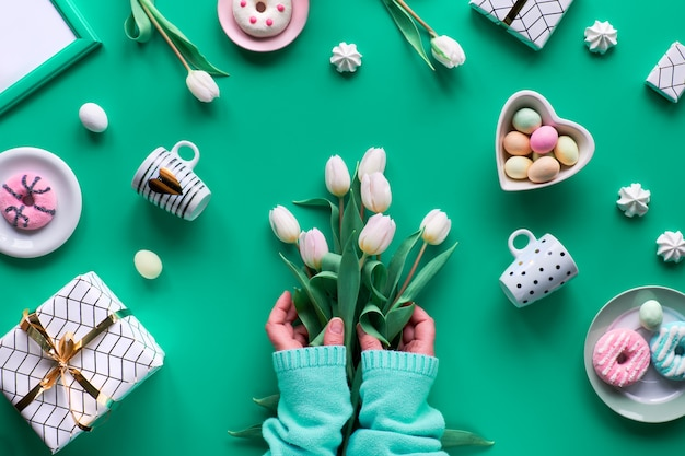Geometric spring flat lay on green mint background. easter, mother day, spring birthday or anniversary in rustic style. hand with white tulips. easter eggs, coffee cups, fresh tulips and doughnuts.