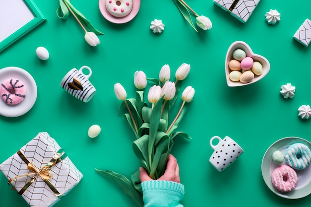 Geometric spring flat lay on green mint background. easter, mother day, spring birthday or anniversary in rustic style. white tulips in hands. easter eggs, coffee cups, fresh tulips and doughnuts