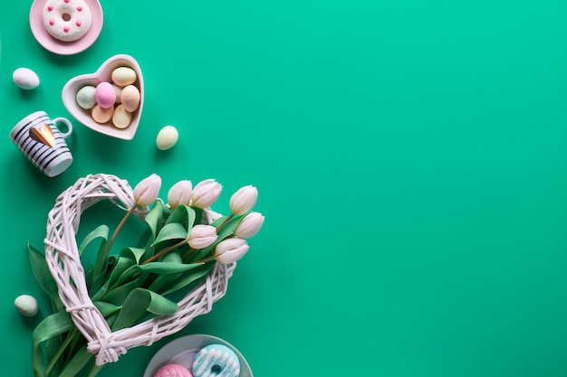 幾何学的な春のフラットは、ピンクの壁に白と緑で横たわっていたイースター、母の日、春の誕生日または記念日。プラスチック熱ライトボード、イースターエッグ、コーヒーメーカー、カップ、チューリップ、ギフト。