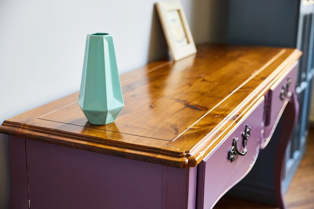Geometric vase and wooden dressing table close-up.
