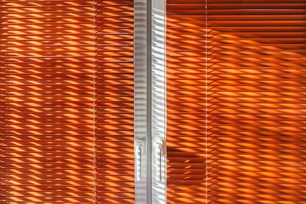 The geometrical beautiful sun's rays on the closed wooden blinds to the window curtain.