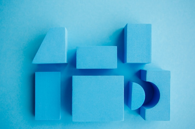 Geometrical figures still life composition. cube and other objects on blue background.