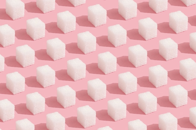 Геометрический узор из кубиков белого сахара на пастельно-розовом фоне. абстрактное, минимальное.