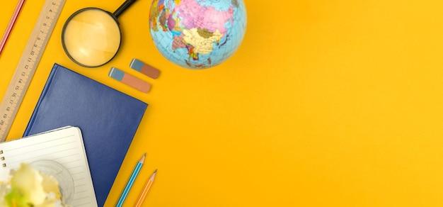 Концепция плоской планировки уроков географии обратно в школу на желтом столе, вид сверху на рабочий стол с ...