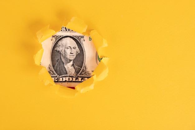 Джордж вашингтон смотрит на однодолларовую купюру из-под желтых клочков бумаги. скопируйте пространство.