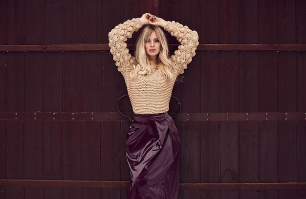 Georgeous elegant blonde in bright dress on wooden background