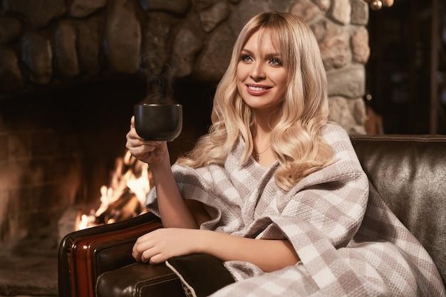 Georgeous elegant blonde under bright plaid near fireplace