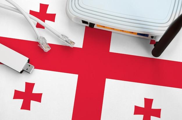 Флаг грузии изображен на столе кабелем internet rj45, беспроводным usb-адаптером wi-fi и маршрутизатором. концепция интернет-связи