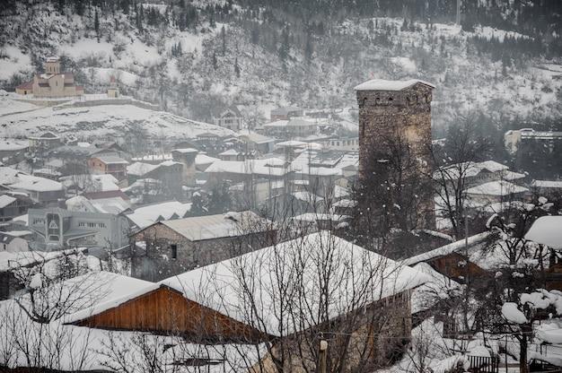 ジョージア、スヴァネティ、メスティア。塔と家が正面にある雪に覆われた旧市街を上から見る