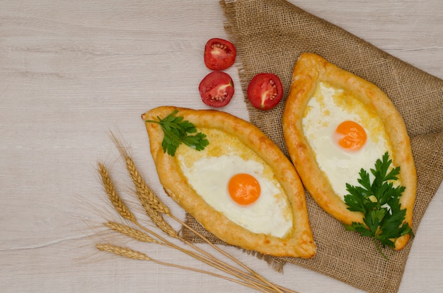 Georgian cheese pie and eggs on sackcloth, ears of wheat and tomatoes