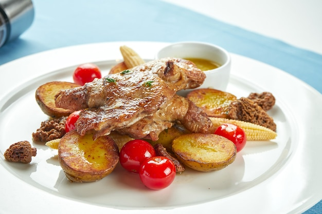 Грузинская куриная тапака с картофелем и овощами-гриль в белой тарелке на синей скатерти. курица-гриль