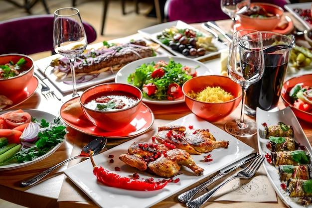 グルジア料理。休日の家族全員のためのさまざまな料理の大きな敷設テーブル。