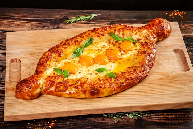 Georgian cuisine. big khachapuri with 5 egg yolks, on a wooden board. a dish in a restaurant for a large company of people. background image copy space