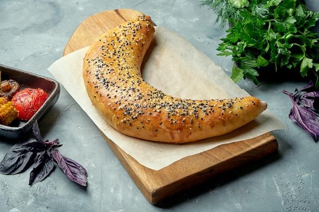 グルジア風料理khachapuri、塩味のチーズとごまの種、グリアンスタイルの木製ボード