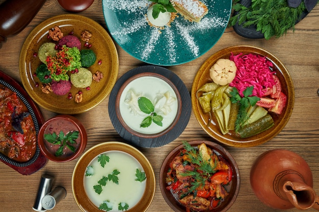 Georgian cuisine foodset from phali, lobio, ojahuri, pickled vegetables, chikhirtma and cake top view food on wooden table