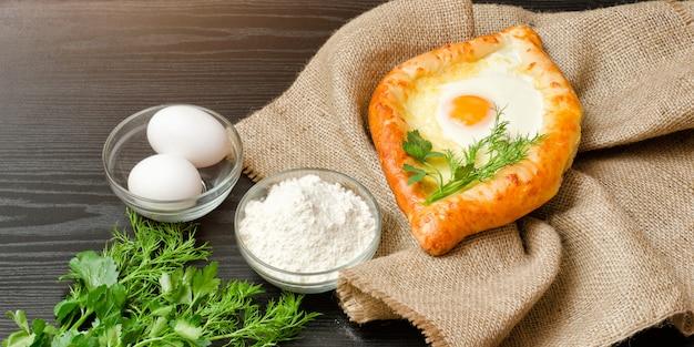 Georgian cuisine. khachapuri on sackcloth, flour, eggs. black table.