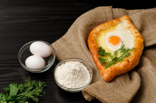 Georgian cuisine. khachapuri on sackcloth, flour, eggs and parsley on black table, closeup