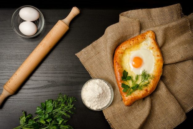 Georgian cuisine. of khachapuri on sackcloth, flour, eggs and rolling pin. black table, space for text