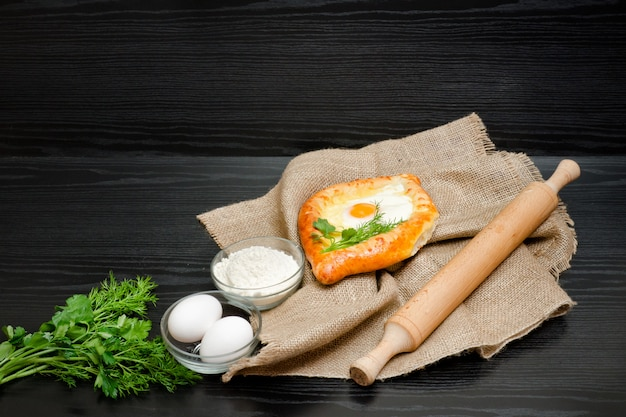 Georgian cuisine, khachapuri on sackcloth, flour, eggs and rolling pin.