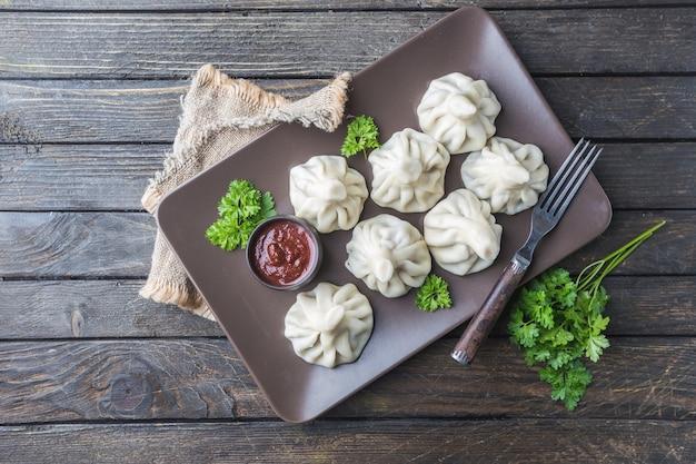 고기, 채소 및 토마토 매운 소스를 곁들인 그루지야 만두 킨 칼리 satsebeli
