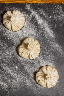 グルジアの餃子ヒンカリと肉と木の板に小麦粉の黒い背景のマキンのプロセス...