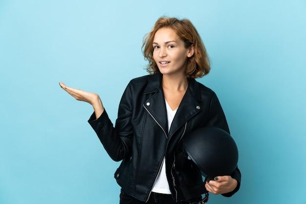 파란색 배경에 고립 된 오토바이 헬멧을 들고 그루지야 소녀는 올 초대를 위해 손을 옆으로 확장