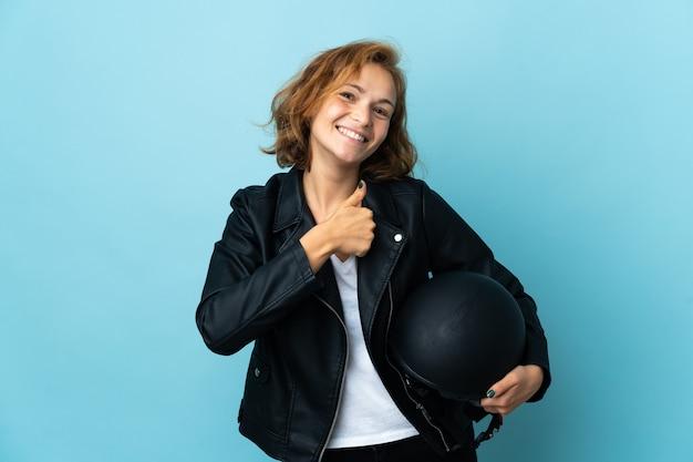 제스처를 엄지 손가락을주는 파란색 배경에 고립 된 오토바이 헬멧을 들고 그루지야 소녀