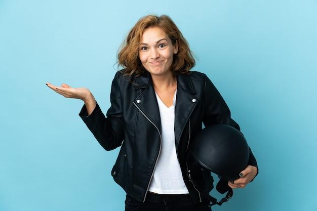 손을 올리는 동안 의심을 갖는 파란색 배경에 고립 된 오토바이 헬멧을 들고 그루지야 소녀