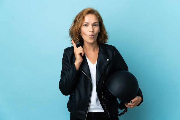 파란색 배경에 고립 된 오토바이 헬멧을 들고 그루지야 소녀는 손가락을 들어 올리는 동안 솔루션을 실현하려고합니다.