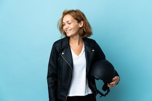 Грузинская девушка держит мотоциклетный шлем на синем фоне, глядя в сторону