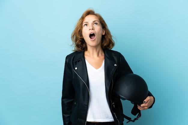 파란색 배경에 격리된 오토바이 헬멧을 들고 놀란 표정으로 올려다보는 그루지야 소녀