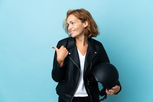 제품을 제시하기 위해 측면을 가리키는 파란색 배경에 고립 된 오토바이 헬멧을 들고 그루지야 소녀