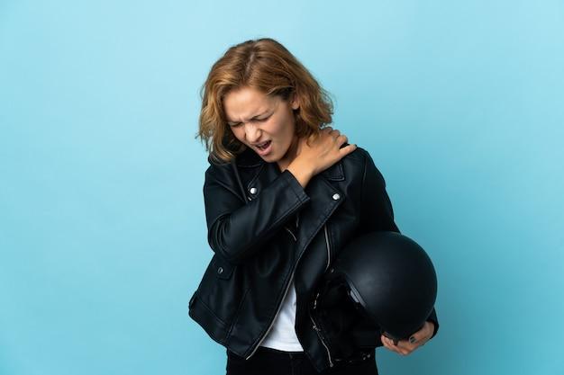 Грузинская девушка, держащая мотоциклетный шлем на синем фоне, страдает от боли в плече из-за того, что приложила усилие