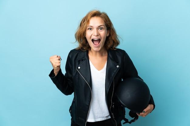 승자 위치에서 승리를 축하하는 파란색에 고립 된 오토바이 헬멧을 들고 그루지야 소녀