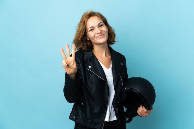 블루 행복에 고립 된 오토바이 헬멧을 들고 손가락으로 세 세 그루지야 소녀