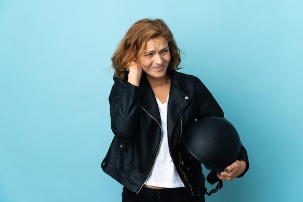 欲求不満と耳を覆っている青い壁に分離されたオートバイのヘルメットを保持しているグルジアの女の子