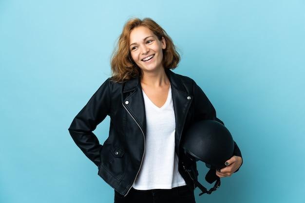 오토바이 헬멧을 들고 그루지야 소녀 엉덩이에 팔을 포즈와 미소 파란색 벽에 고립