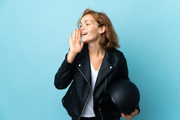 파란색 벽에 고립 된 오토바이 헬멧을 들고 그루지야 소녀 입 벌리고 측면으로 외치는